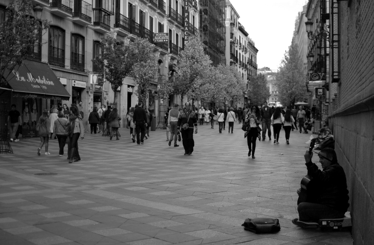 A black and white photo of a man playing guitar as people pass him on the street in Madrid, Spain